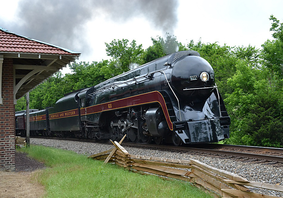 The Class J #611 passes the old passenger depot at The Plains